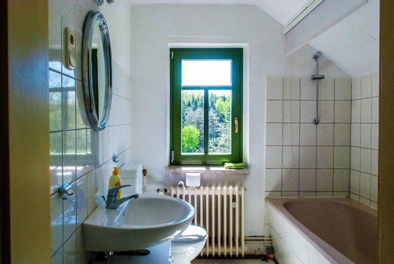 Bad mit Wanne, Toilette, Waschbecken, Spiegel und Fenster im Jagdhaus
