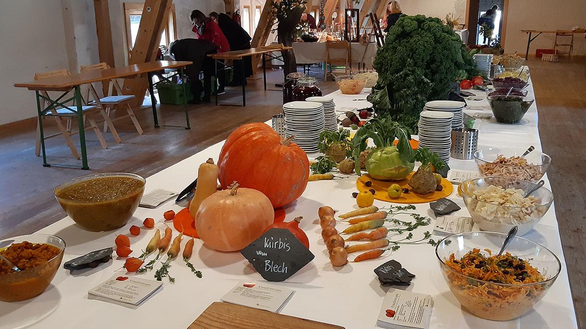 Langer Tisch im Heubodensaal ist gedeckt mit Krautarten, Kürbissen, Rüben, Krautsalaten und anderem Gemüse