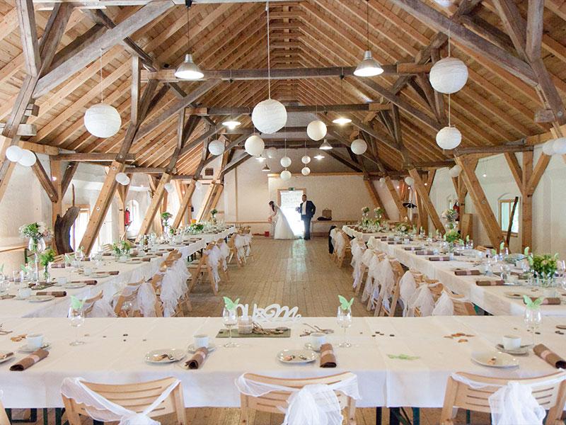 Hochzeitspaar im Heubodensaal mit festlich gedeckten Tafeln