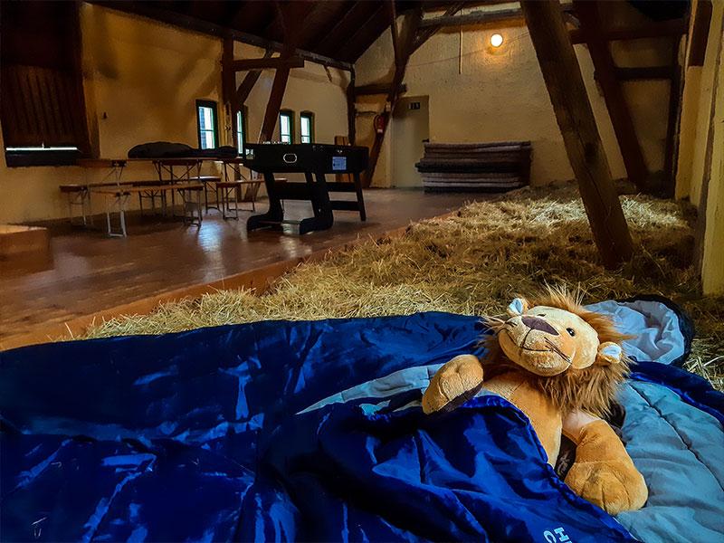 Schlafsäcke mit Kuscheltier im Heu, im Hintergrund ein Kickertisch und Matratzen