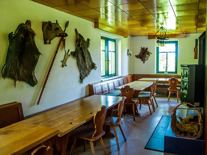 Jagdhaus Veranstaltungsraum mit Holztischen, Fellen an den Wänden und einem Kachelofen