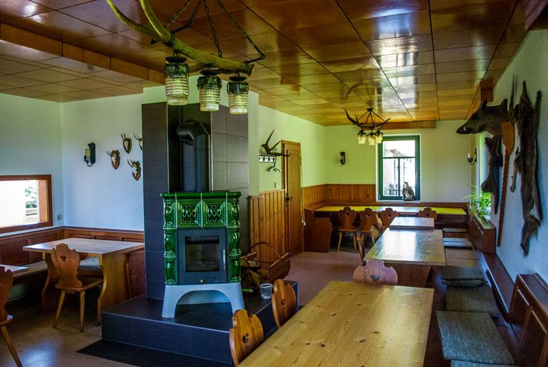 Jagdhaus Veranstaltungsraum mit einer Durchreiche zur Küche, Holztischen, Fellen an den Wänden und einem Kachelofen
