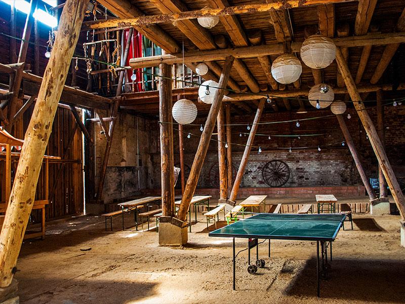 Innenraum der Scheune mit Holzbalken, Sitzbänken, Kugellampen und einer Tischtennisplatte