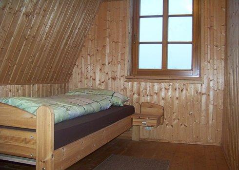 Einzelbett in holzvertäfeltem Schlafzimmer in der Gesindewohnung