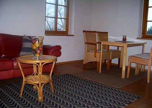 Tisch mit Stühlen und Sofa mit kleinem Tischchen im Wohnzimmer der Gesindewohnung