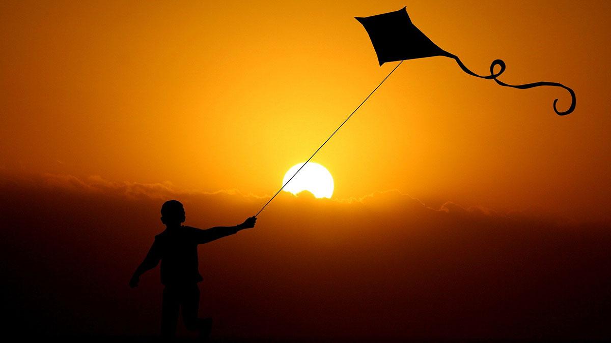 Kind mit Drachen vor Sonnenuntergang